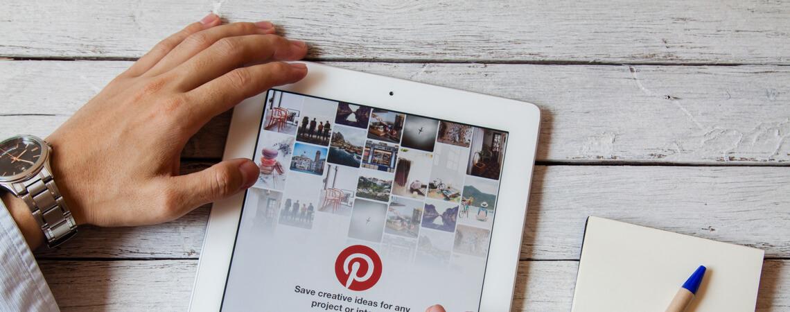 Hände mit Tablet und Pinterest-Seite