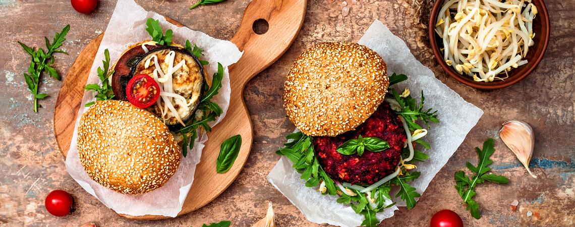 Zwei Veggies-Burger servierten auf Schneidbrett auf steinigem Hintergrund