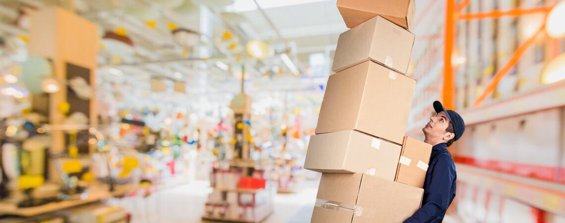 Mann mit vielen Kartons im Logistiklager