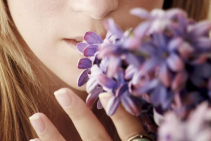 Frau riecht an Blüten