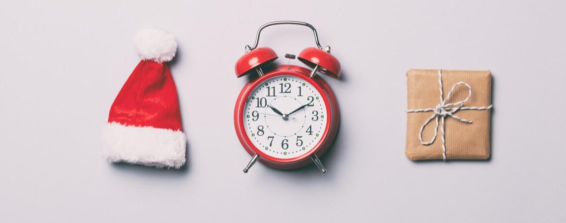 Weihnachtseinkäufe: Mütze, Wecker und Geschenk liegen nebeneinander
