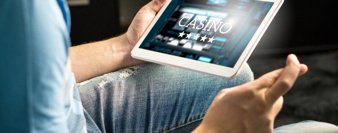 Mann, der am Tablet ein Online-Casino öffnet.
