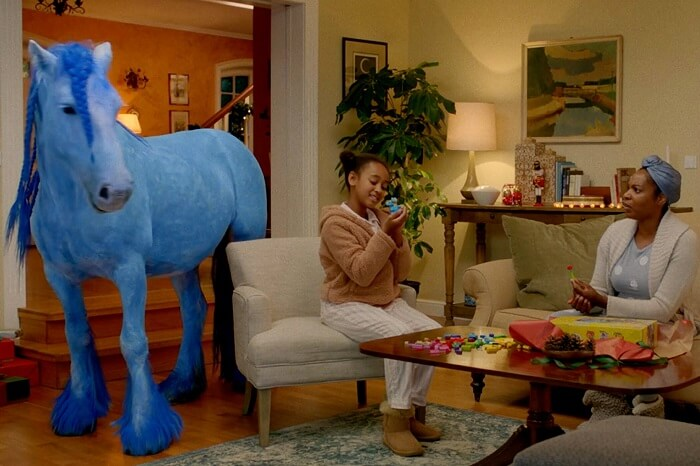 Blaues Pferd und Lego-spielende Kinder und Erwachsene im Wohnzimmer