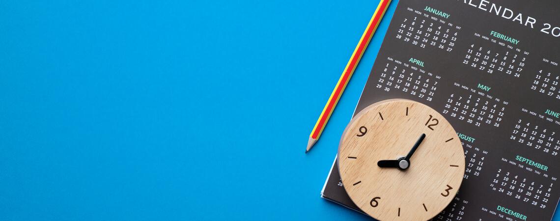 Kalender und Uhr auf blauem Hintergrund