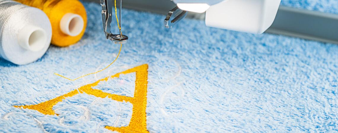 Gelbes A wird auf ein blaues Handtuch gestickt