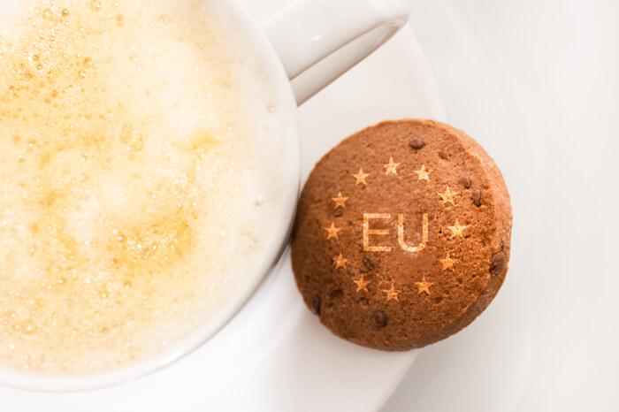 Keks mit der Aufschrift EU und Sternen liegt neben einer Tasse Kaffee