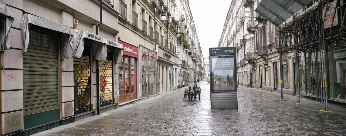 Leere Einkaufsgasse mit geschlossenen Geschäften.