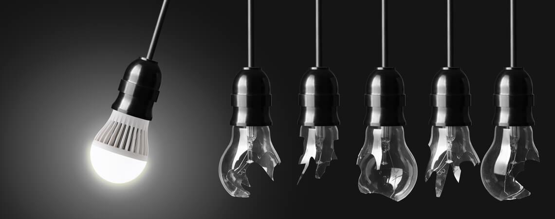 Eine leuchtende Lampe schwingt gegen kaputte Glühbirnen