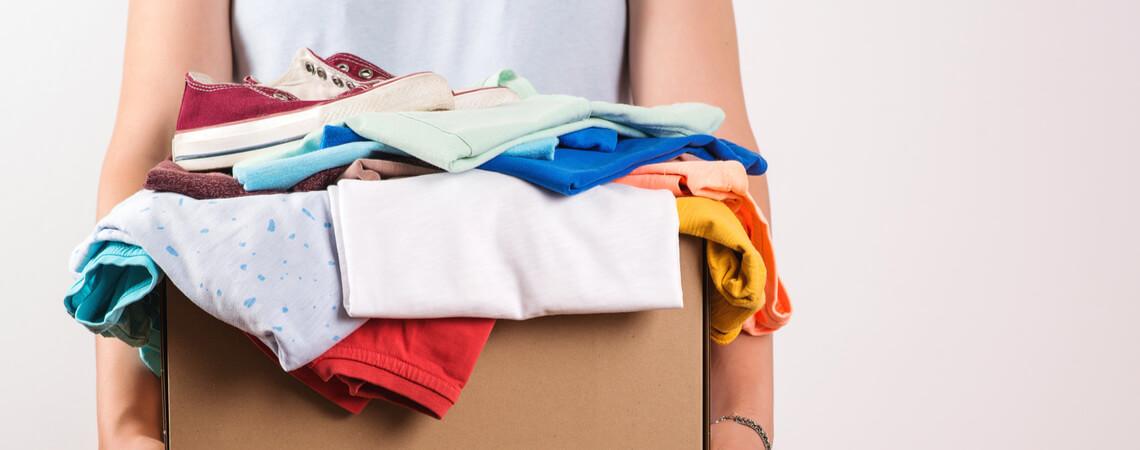 Frau mit Kiste gebrauchte Kleidung