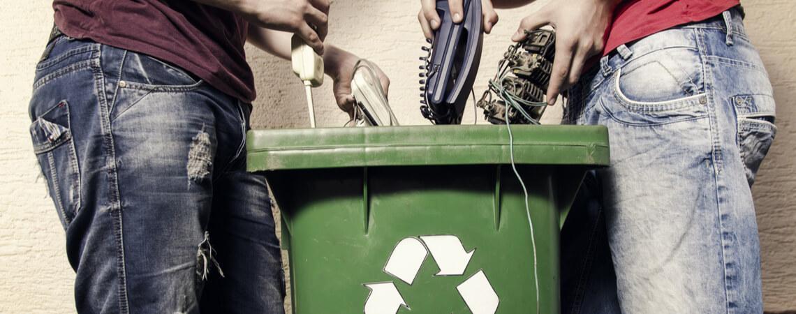 Junge Männer werfen Elektroschrott in eine Tonne