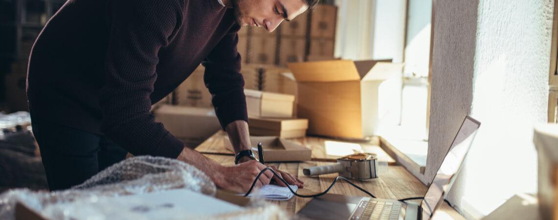 Unternehmer mit Kartons Schreibtisch