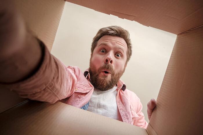 Mann schaut überrascht in Karton