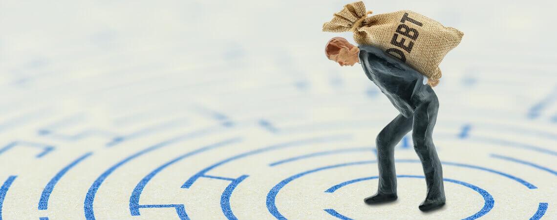 Geschäftsmann trägt Schulden-Sack durch ein Labyrinth