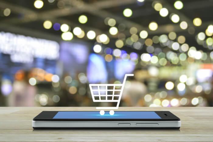 Smartphone mit Einkaufswagensymbol und eine Einkaufsmeile im Hintergrund