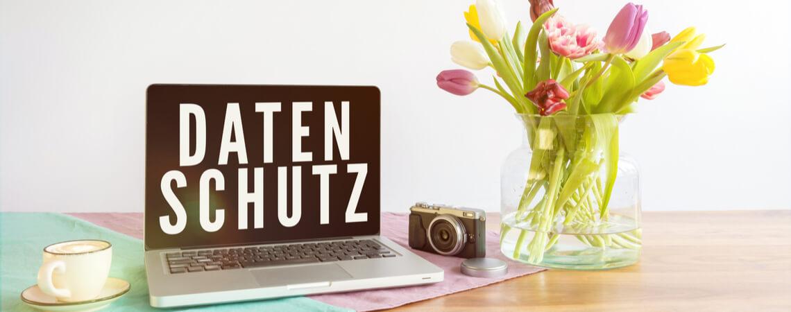 Laptop mit Datenschutzschrift auf Frühlingstisch