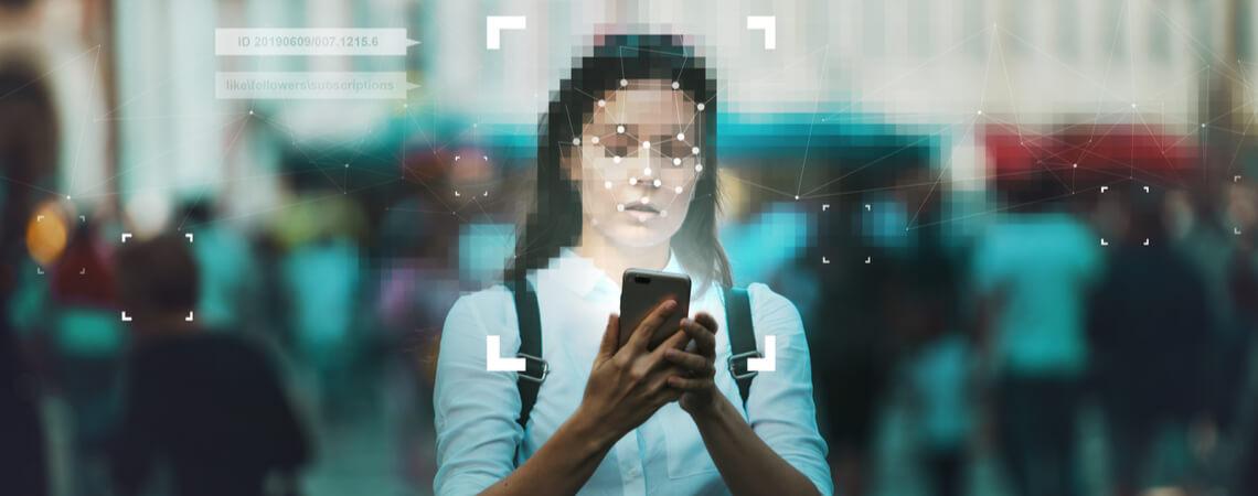 Gesicht von Frau mit Smartphone wird digital ausgewertet