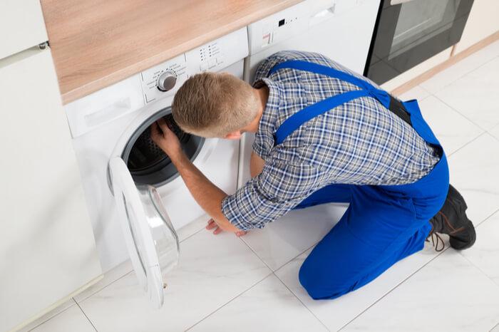 Monteur repariert Waschmaschine