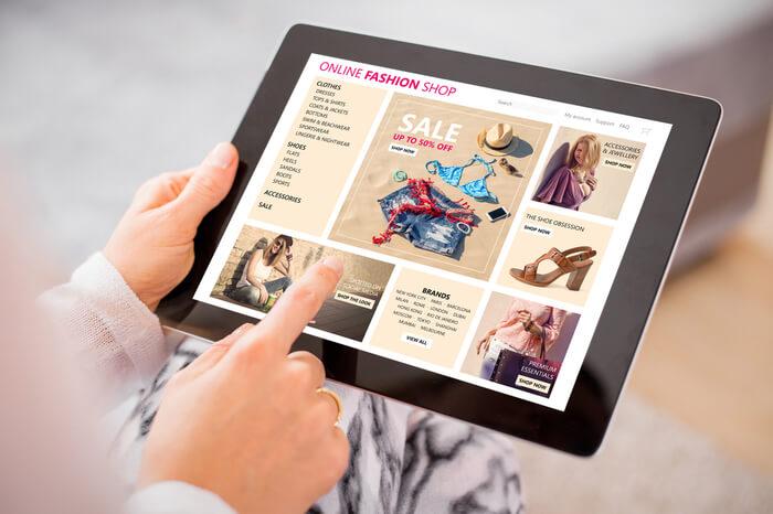 Frau kauft online am Tablet Kleidung ein