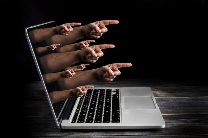 Hände zeigen aus Notebook heraus