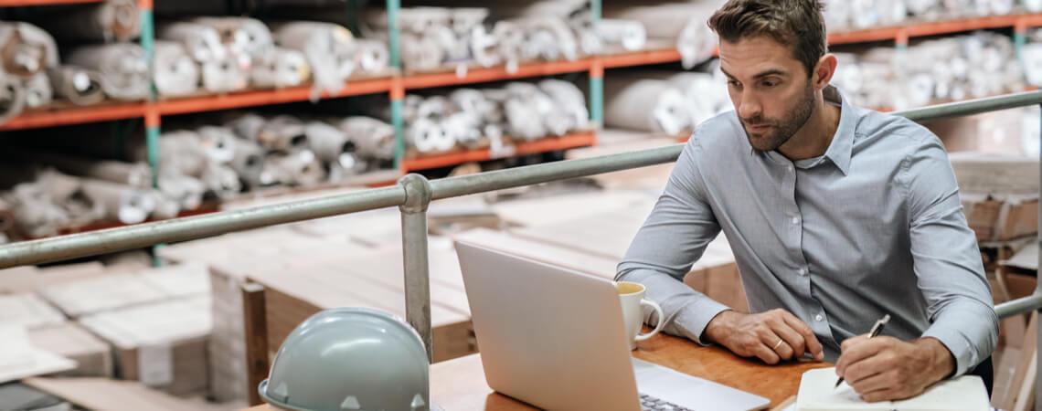 Online-Händler sitzt im Lager am Laptop