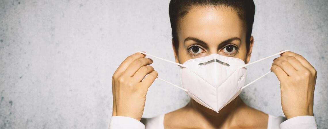Frau setzt FFP2-Maske auf