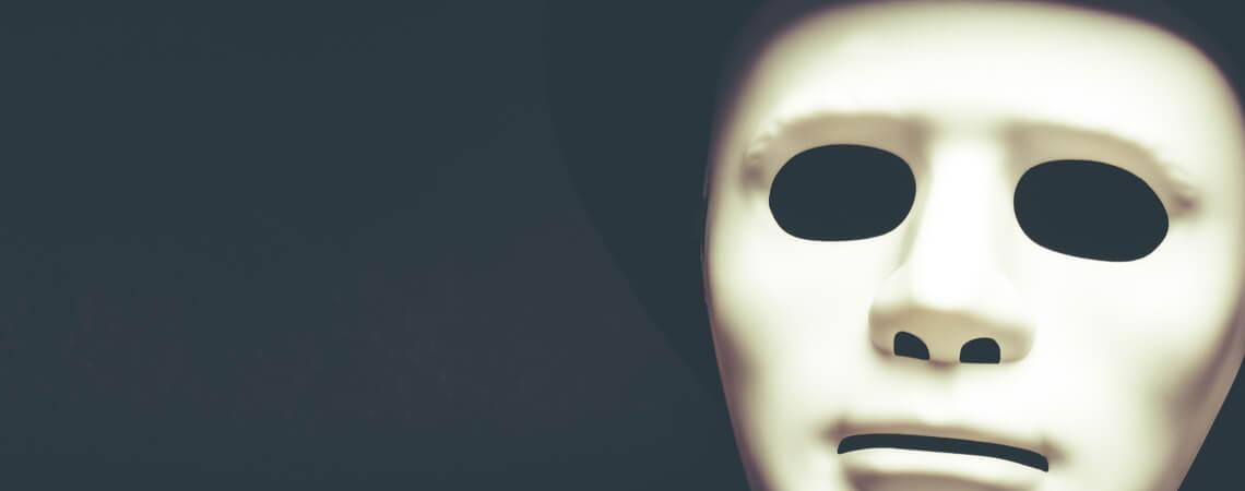 betrug mit falscher Identität_ Weiße Maske auf schwarzem Grund
