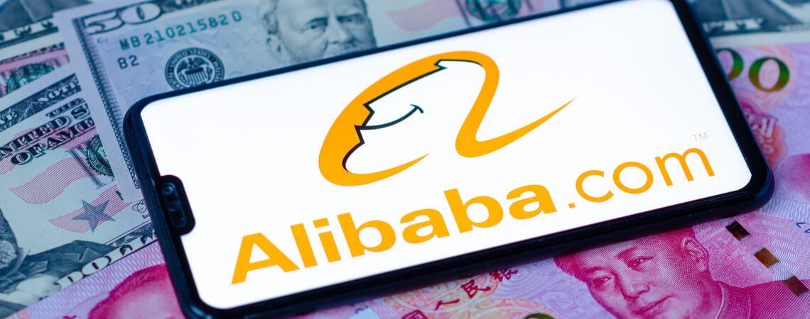 Alibaba auf Smartphone mit Geldscheinen