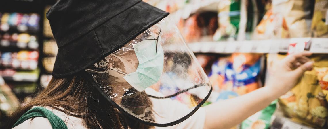 Frau kauft mit Maske und Visier Lebensmittel ein