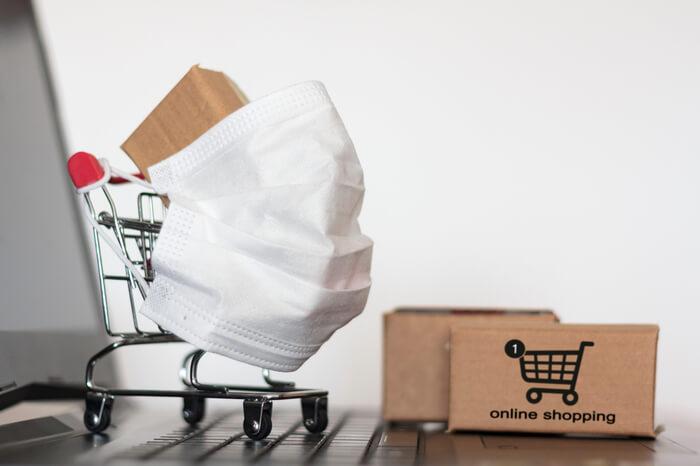 Einkaufswagen mit Schutzmaske vor Laptop