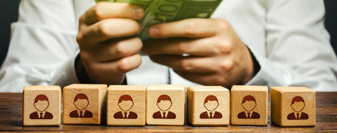 Ein Mann zählt Geld in seinen Händen über Holzwürfel mit Symbolen der Angestellten.
