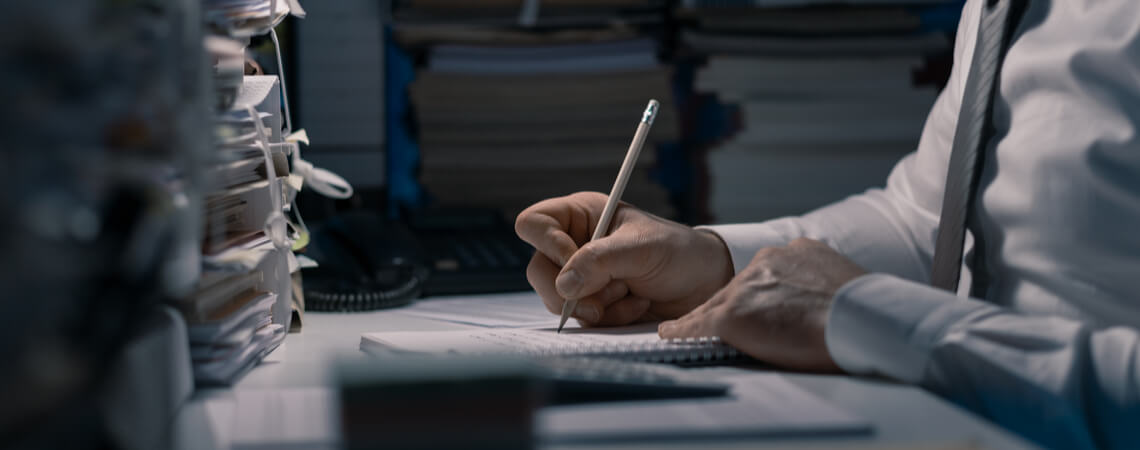 Mann schreibt mit Stift auf Zettel