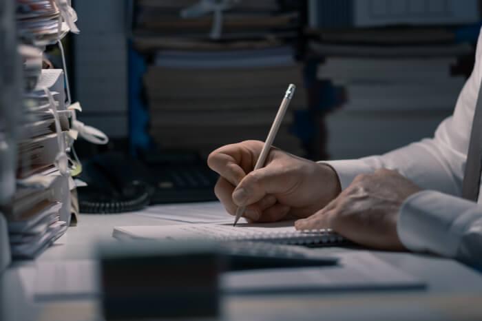 Mann schreibt vor Papierstapel