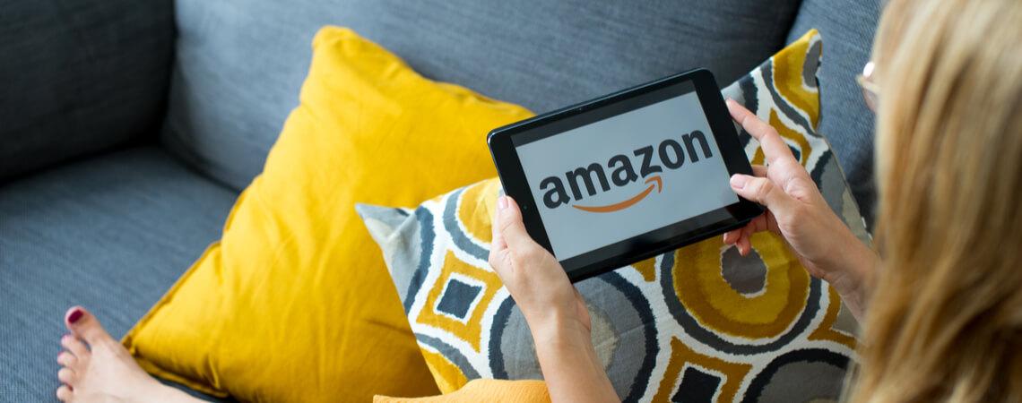 Frau mit Amazon-Tablet auf farbenfrohem Sofa