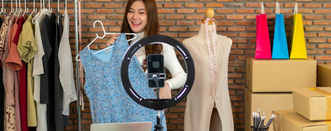 Frau zeigt Kleid in Kamera