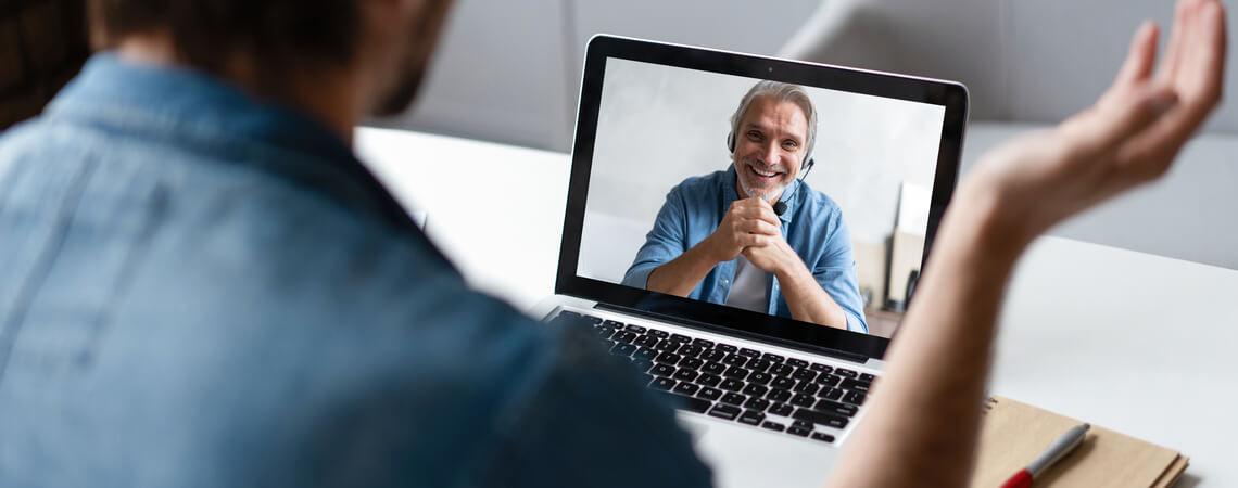Mann in Videokonferenz vor Laptop