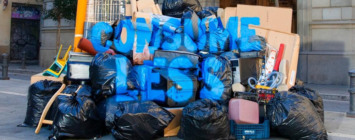 Consume Less Schriftzug auf Müllberg