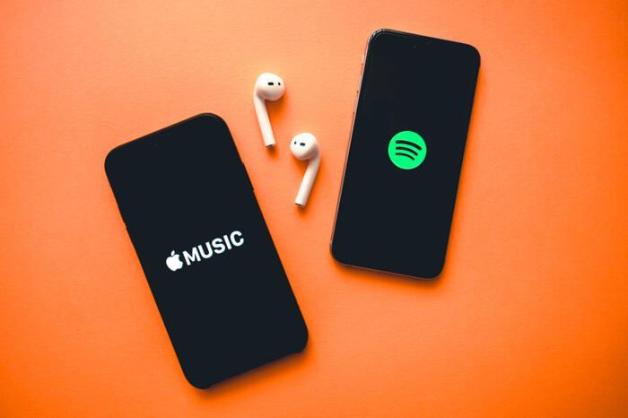 Apple und Spotify-Logos auf Smartphones