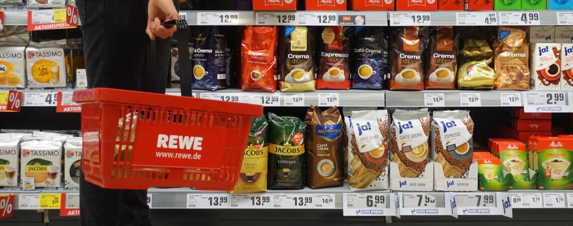 Kunde mit Einkaufskorb im Rewe-Supermarkt