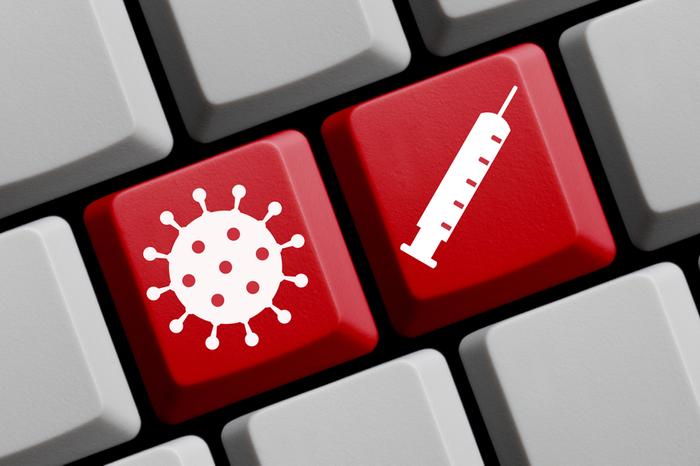 Tastatur mit Spritze und Virus-Bildern
