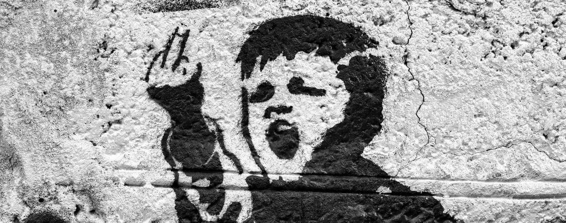 Graffiti über Wut: Junge, der einen Stinkefinger zeigt
