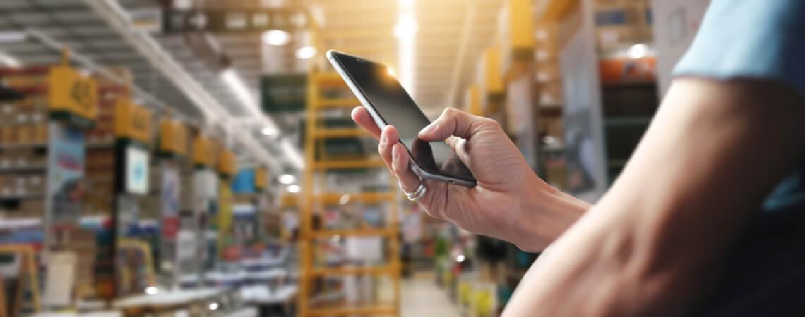 Digitalisierung im Großhandelslager Mann mit Smartphone