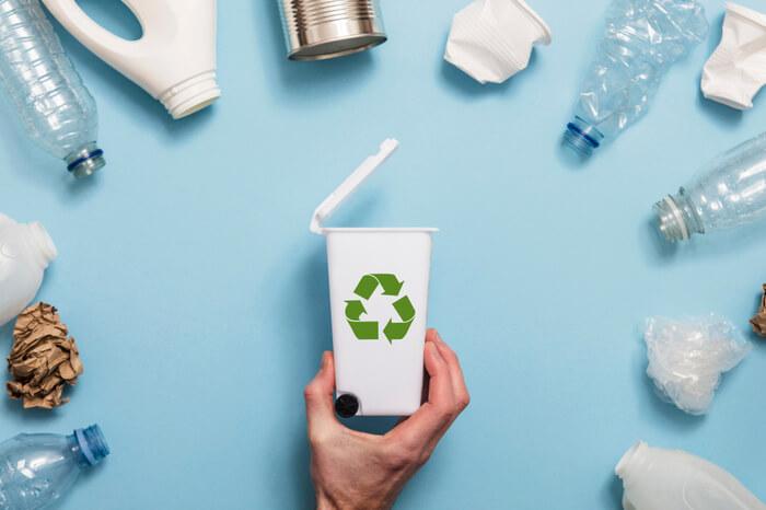 Hand, die einen Abfallbehälter mit viel Abfallverpackung hält