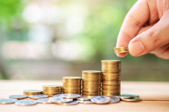 Mensch türmt Geldmünzen auf