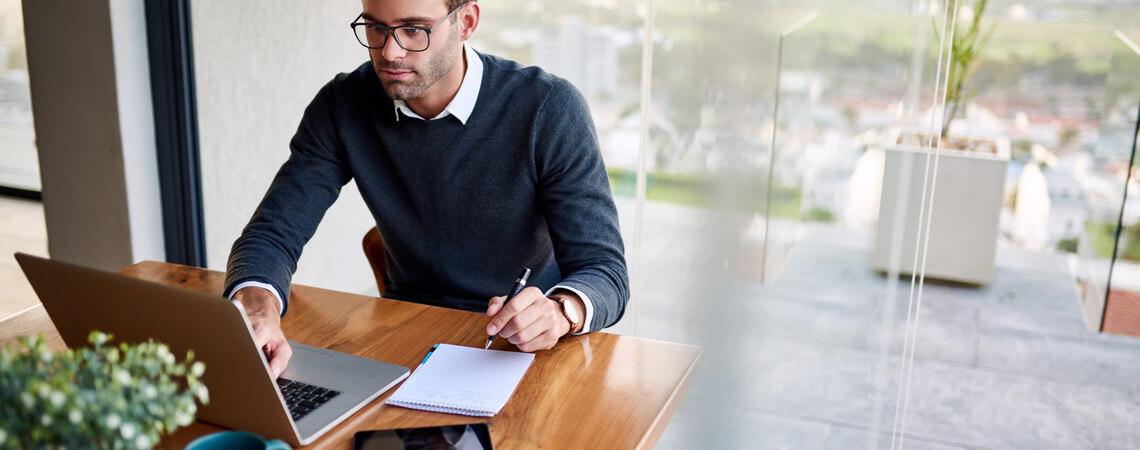 Unternehmer sitzt am Laptop