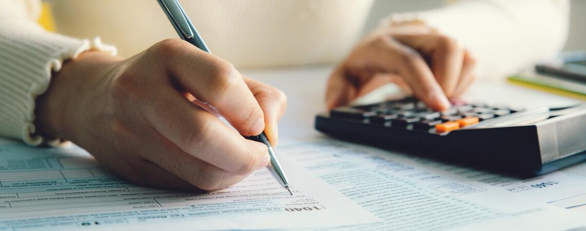 Person mit Taschenrechner erledigt Mehrwertsteuer