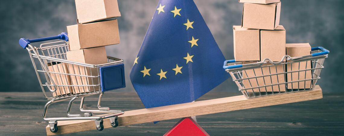 Waage mit Mini-Einkaufswagen vor EU-Flagge
