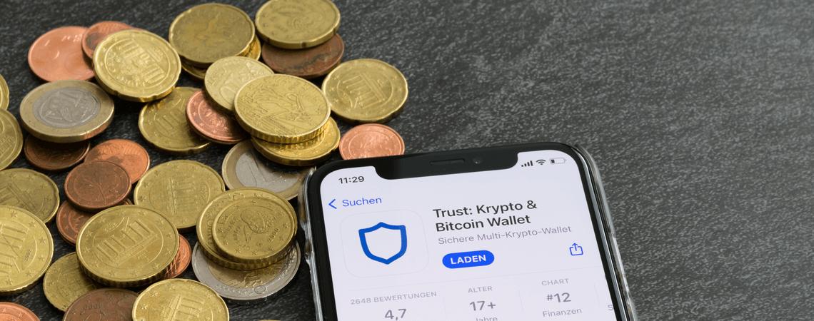 Münzen und Handy mit Kryptowallet App