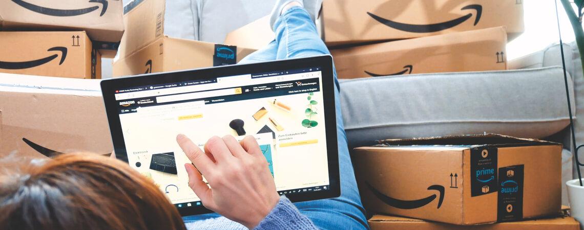 Person tippt auf Tablet vor Amazon-Paketen