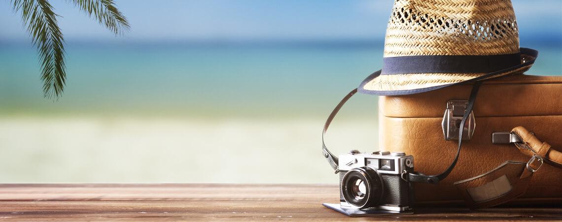 Koffer, Sonnenhut und Kamera am Strand