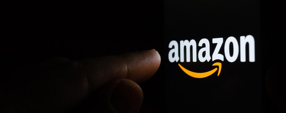 Finger zeigt auf ein Amazon-Logo